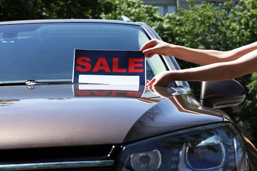 putting for sale sign on brown car outide