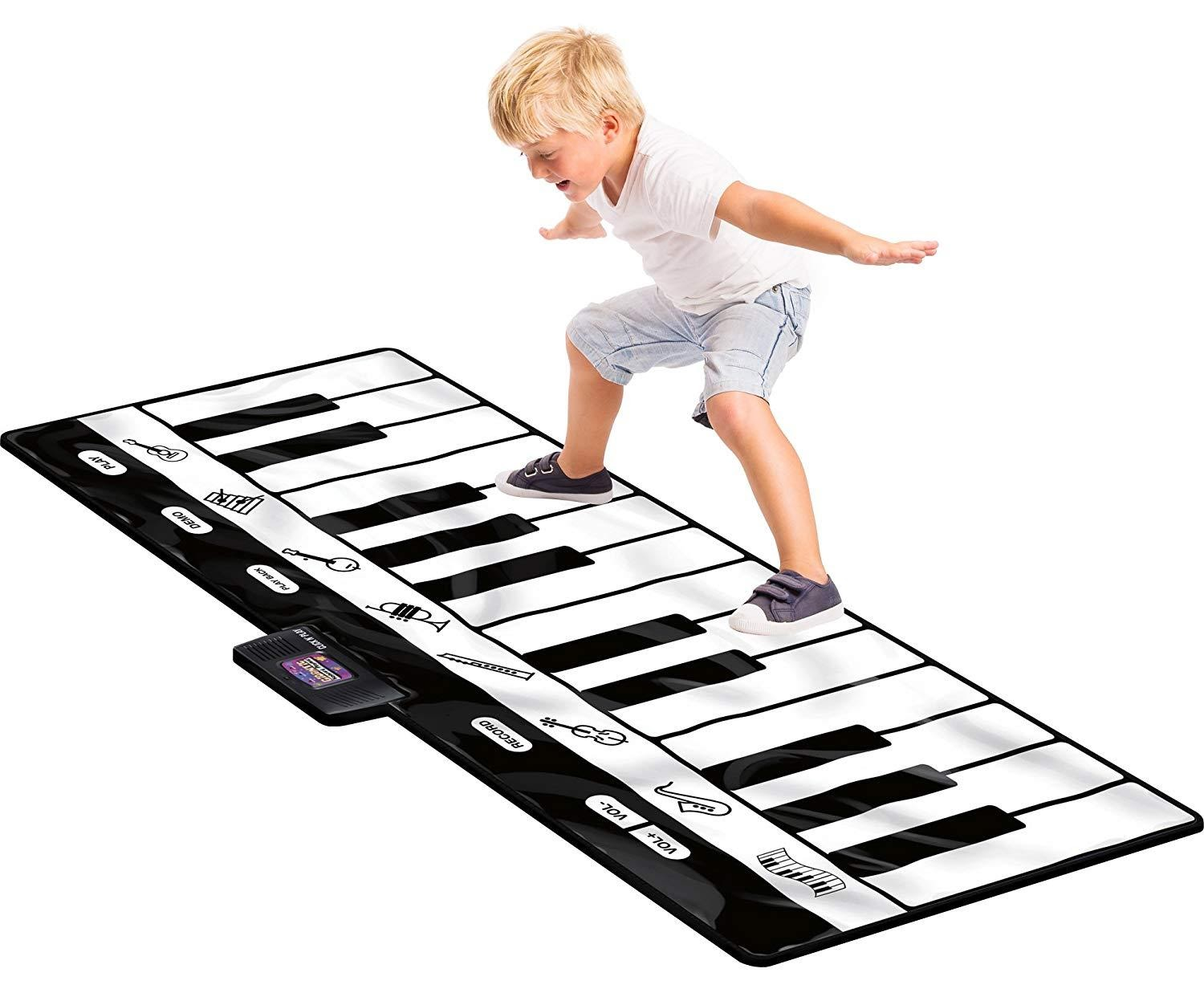 blod boy standing playing on keyboard play mat on white background